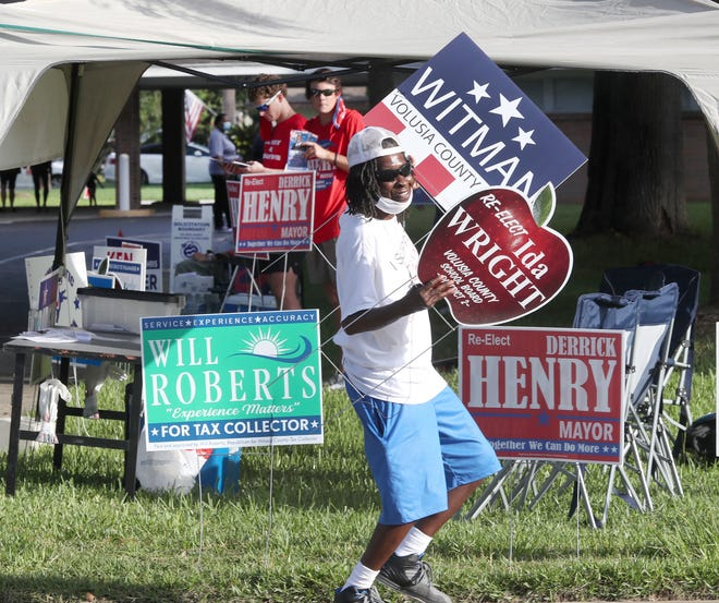 Sylvia Jenkins dances and swings campaign signs to get the attention of passing motorists on election day Tuesday at the Beville Road Church of God in Daytona Beach.