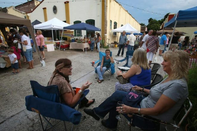 Friends enjoy a drink during the DeLand Artisan Alley Farmers Market, held every Friday evening, while chatting outside Nest, a gift shop with a small bar. The DeLand City Commission on Monday, Aug. 17, 2020, approved a resolution that will allow to-go alcoholic drinks in downtown as well as more tables and chairs outside so that people can eat and drink more comfortably amid the coronavirus pandemic.