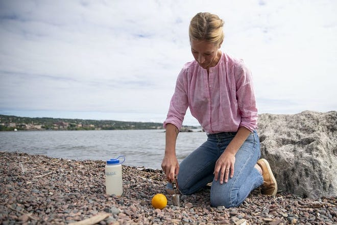 Emily Vikre sat on the shore of Lake Superior in Duluth on Monday as she demonstrated how to make an Old Fashioned.