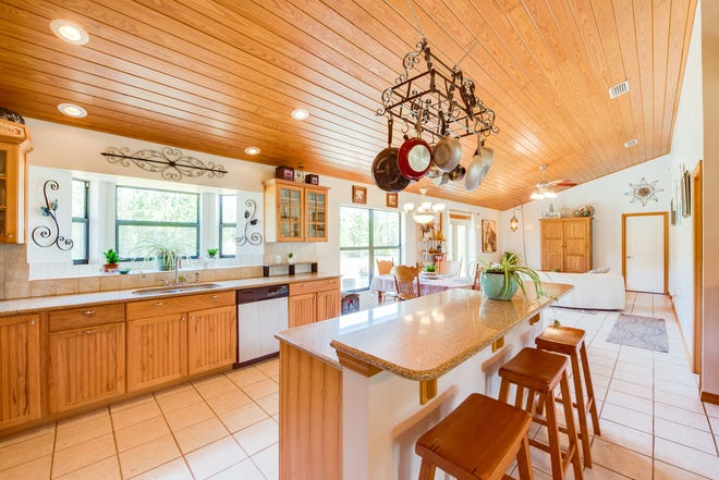 Topped with a beautiful tongue-and-groove ceiling, the updated and open kitchen features solid-wood cabinetry, granite countertops, an island, with a breakfast bar, and newer stainless-steel appliances.