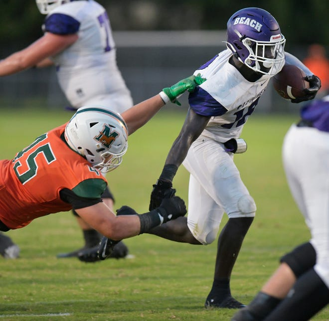 Fletcher running back Myles Montgomery (18) attempts to break free from Mandarin defensive lineman Gavin Adams (45) in their season finale football game in 2019. High school teams in Duval County are set to begin their seasons Sept. 11. [Will Dickey/Florida Times-Union]