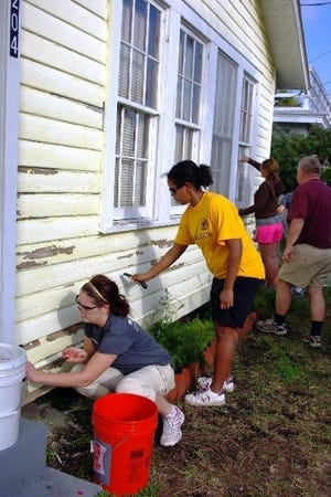 Volunteers are shown painting a house as part of Habitat's A Brush with Kindness initiative. Beaches Habitat has launched a similar program to help senior citizens with home repairs.
