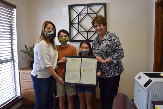 Rep. Kathy Edmonston gave a framed copy of her resolution to the Roussa family.