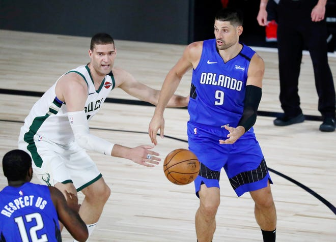 Orlando Magic center Nikola Vucevic (9) passes the ball to forward Gary Clark (12) in front of Milwaukee Bucks center Brook Lopez (11) during the first half of Game 1 of an NBA first-round playoff serie, Tuesday in Lake Buena Vista.