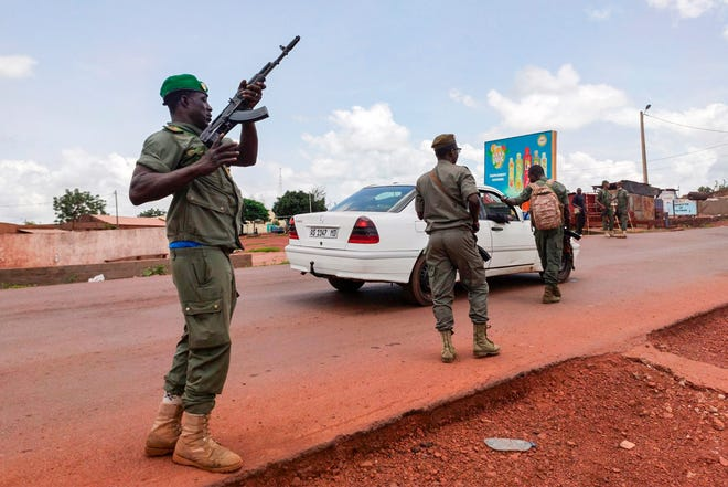 Malian soldiers check a vehicle in the garrison town of Kati, Mali, on Tuesday. Malian soldiers took up arms and began detaining senior military officers in an apparent mutiny, raising fears of a potential coup after several months of anti-government demonstrations calling for the president's resignation.