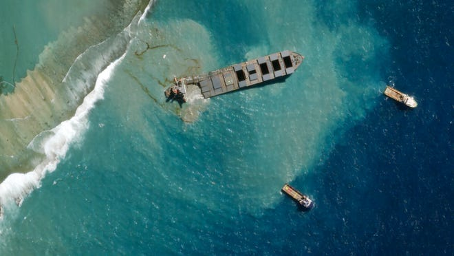 A satellite photo provided Monday by 2020 Planet Labs, Inc. shows the MV Wakashio, a bulk carrier ship that recently ran aground off the southeast coast of Mauritius. The grounded Japanese ship that leaked tons of oil near protected areas off this Indian Ocean island nation has split apart, with remaining fuel spreading into the turquoise waters.