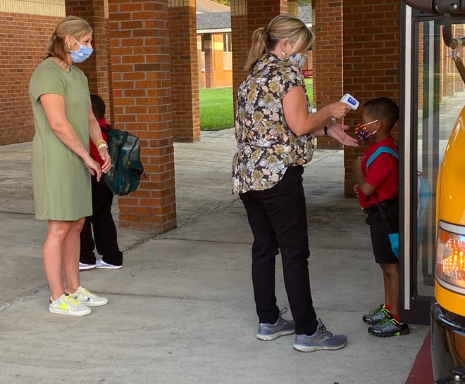 Crescent Elementary School principal Gina LoBue takes a student' temperature at the start of the school Tuesday. Also shown is school counselor Claudia Bourgeois.
