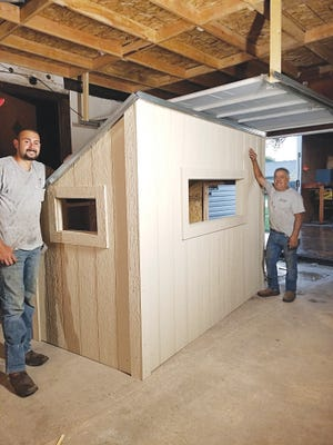 Macias Construction owner Esai Macias (left), explains the concept behind a Facebook-giveaway tree house that will be delivered in early September to Erick Alacla of Great Bend. Employee Jose Gonzales helped build the promotional product that will set on six-foot stilts with a ladder for access.