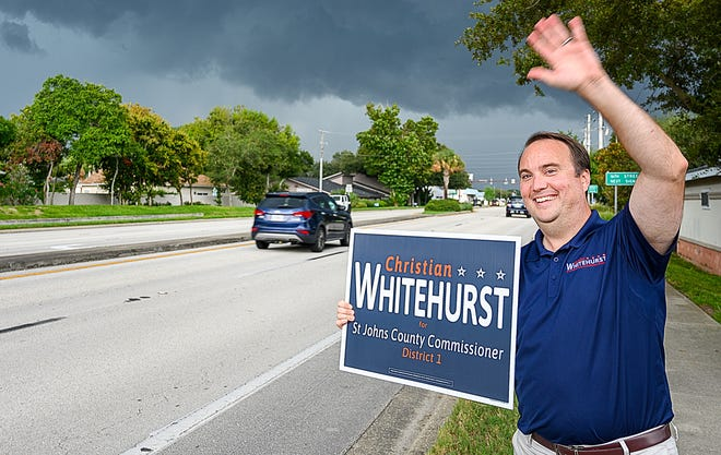 Christian Whitehurst, a Republican candidate for the St. Johns County Commission District 1 seat, waves at people on primary election day Tuesday in St. Augustine Beach. [PETER WILLOTT/THE RECORD]