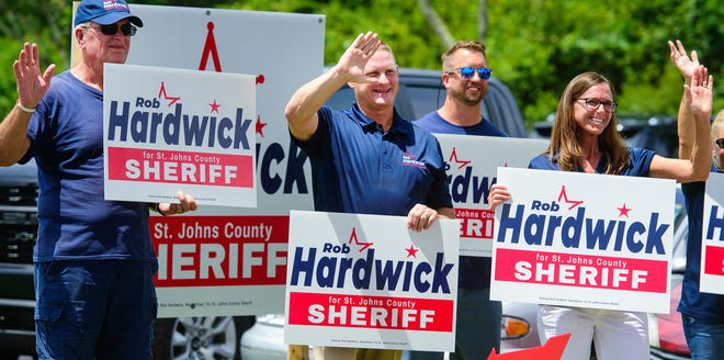 Republican candidate for St. Johns County Sheriff Robert Hardwick, center, waves with a group of his supporters to voters in front of a polling station on Wildwood Drive in St. Augustine on primary election day Tuesday, August 18, 2020.