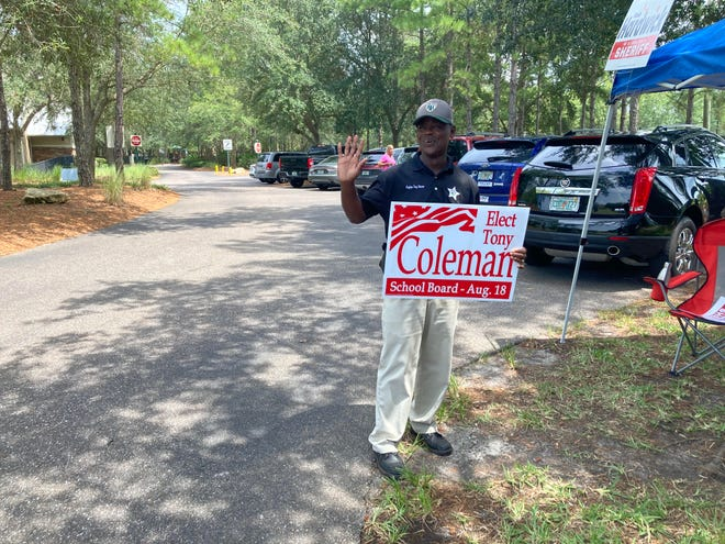 Tony Coleman waves near the Heritage Landing polling place on Tuesday.