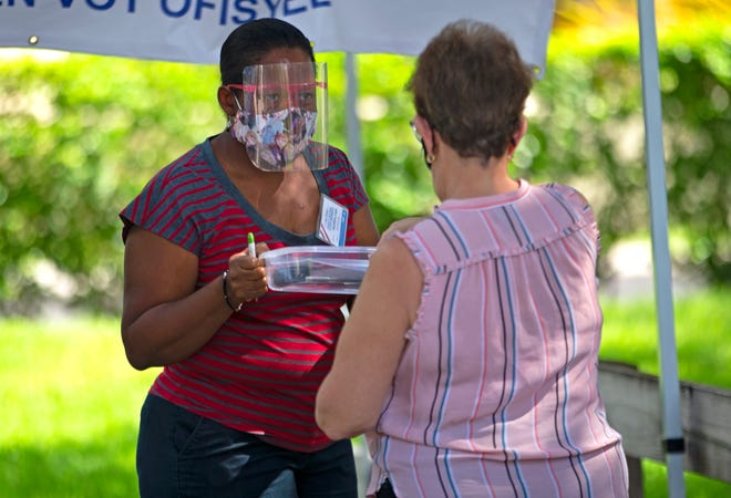 A poll worker helps citizen to check in during the early voting for primary election at Miami Lakes Community Center in Hialeah on Aug. 13.