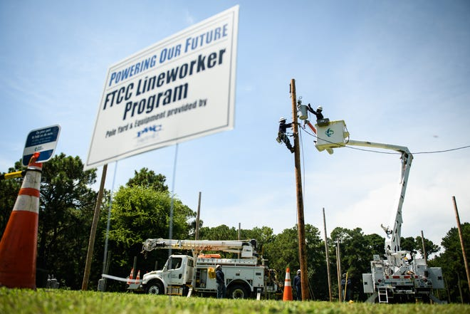 Duke Energy lineworkers put up a utility pole during a demonstration at Fayetteville Technical Community College's pole farm on Tuesday.