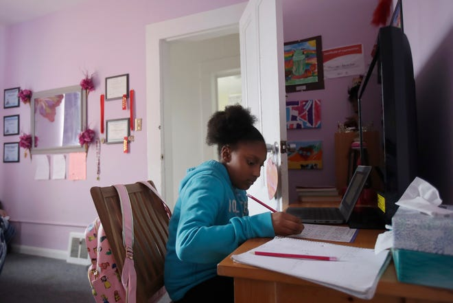 A fourth grader does school work in her room at her family's home. [AP Photo/Jeff Chiu, File]