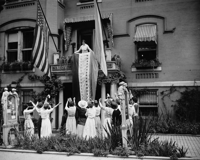 In this Aug. 19, 1920, photo, Alice Paul, chair of the National Woman's Party, unfurls a banner after the ratification of the 19th Amendment, from a balcony at the NWP's headquarters in Washington. [The Crowley Company/Library of Congress via AP]