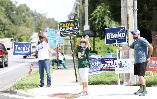 Candidates and supporters wave to motorists on Election Day outside the Millhopper Branch Library on Tuesday in Gainesville. [Brad McClenny/Staff photographer]