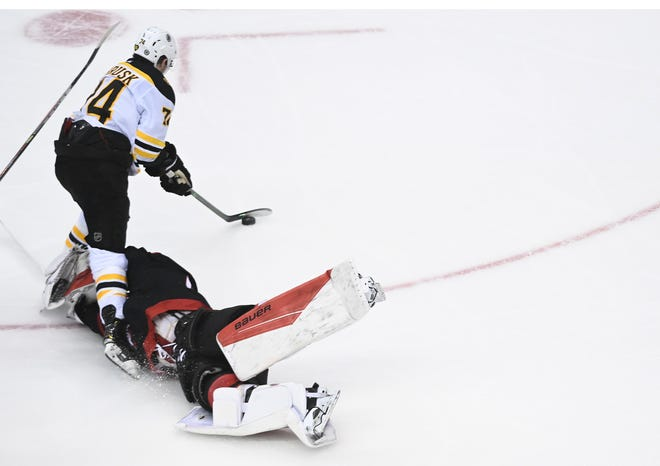 Boston winger Jake DeBrusk, top, beats Hurricanes goaltender James Reimer in a race to the puck, leaving him with a vacant net to score on.