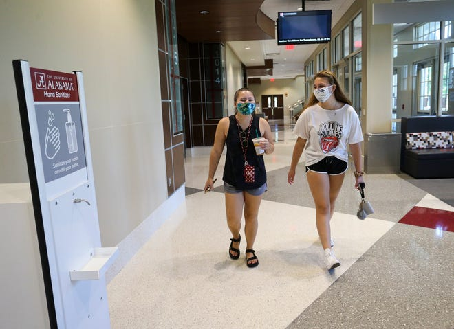 Students Jessica Soares and Rachel Goodman walk past a hand sanitizing station in North Lawn Hall. The University of Alabama showed the measures they have taken to help make the campus safe for faculty and students Tuesday, August 18, 2020. [Staff Photo/Gary Cosby Jr.]