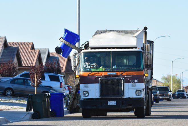 A Burrtec Waste Industries garbage truck lifts a container in Adelanto in March 2020.