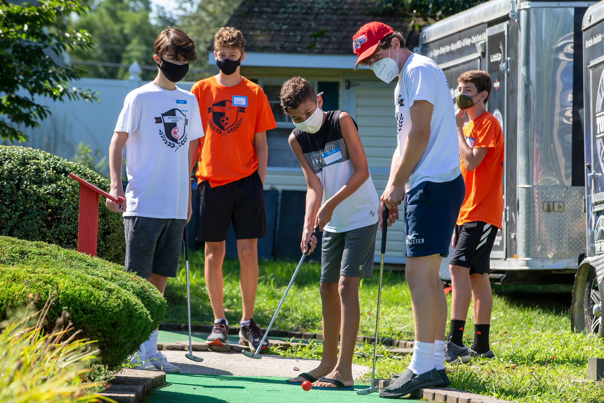 (right in hat) Christian Sanford, 15 of Middletown and jv soccer player helps (center) Blake Illingworth, 13, of Middletown with his swing as members of the Middletown North boys soccer team play mini-golf with a group of special-needs kids as part of Friends Connect Foundation, a nonprofit run by Sophia Ziajski, 19, of Middletown, atTST BBQ & Mini Golf in Middletown, NJ Tuesday, August 18, 2020.