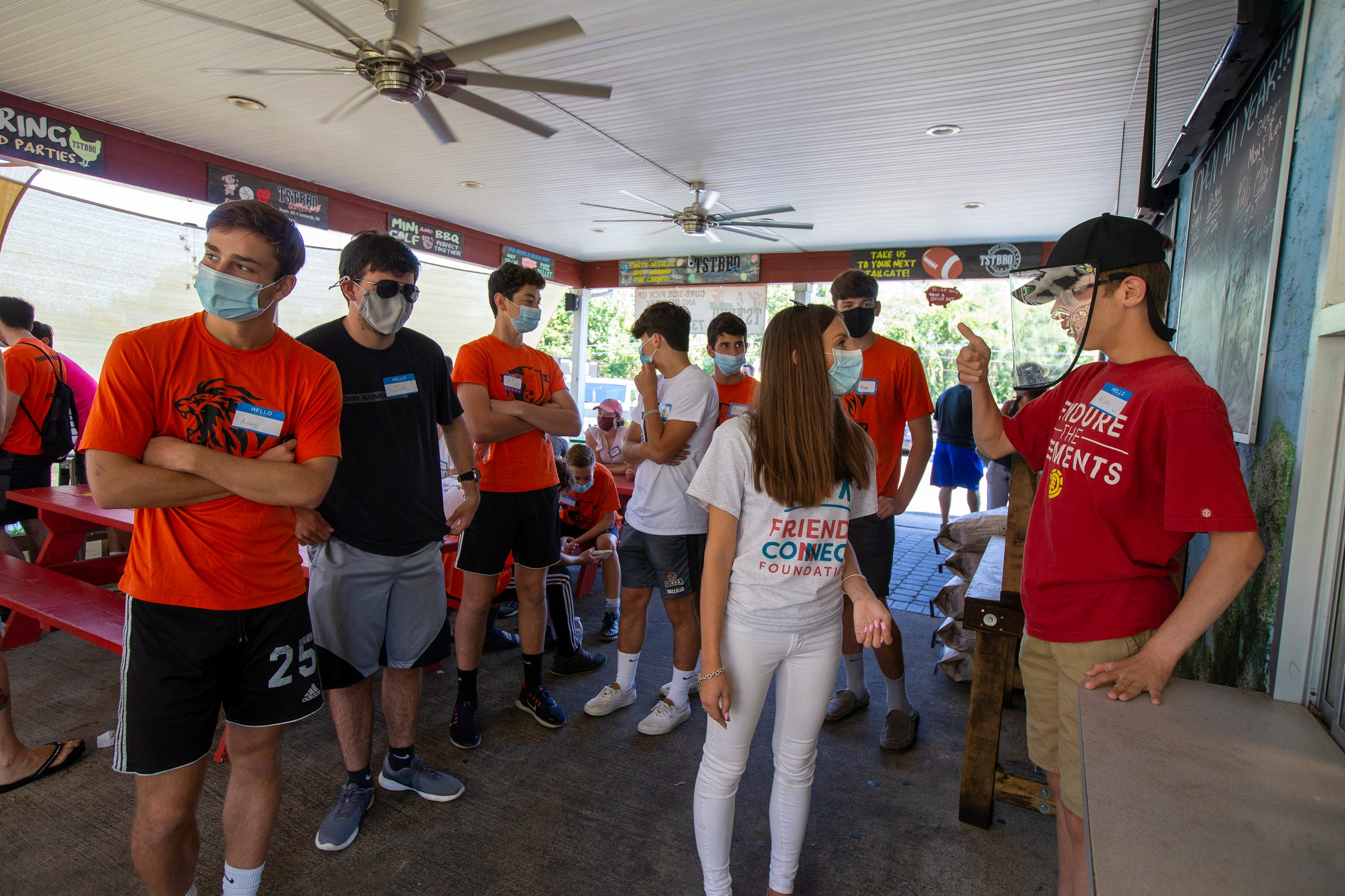 (center Sophia Ziajski, 19 of Middletown,  who runs the Friends Connect Foundation, introduces (right) Matty Driscoll, 16, of Fair Haven to members of the Middletown North boys soccer team before playing mini-golf as part of Friends Connect Foundation at TST BBQ & Mini Golf in Middletown, NJ Tuesday, August 18, 2020.