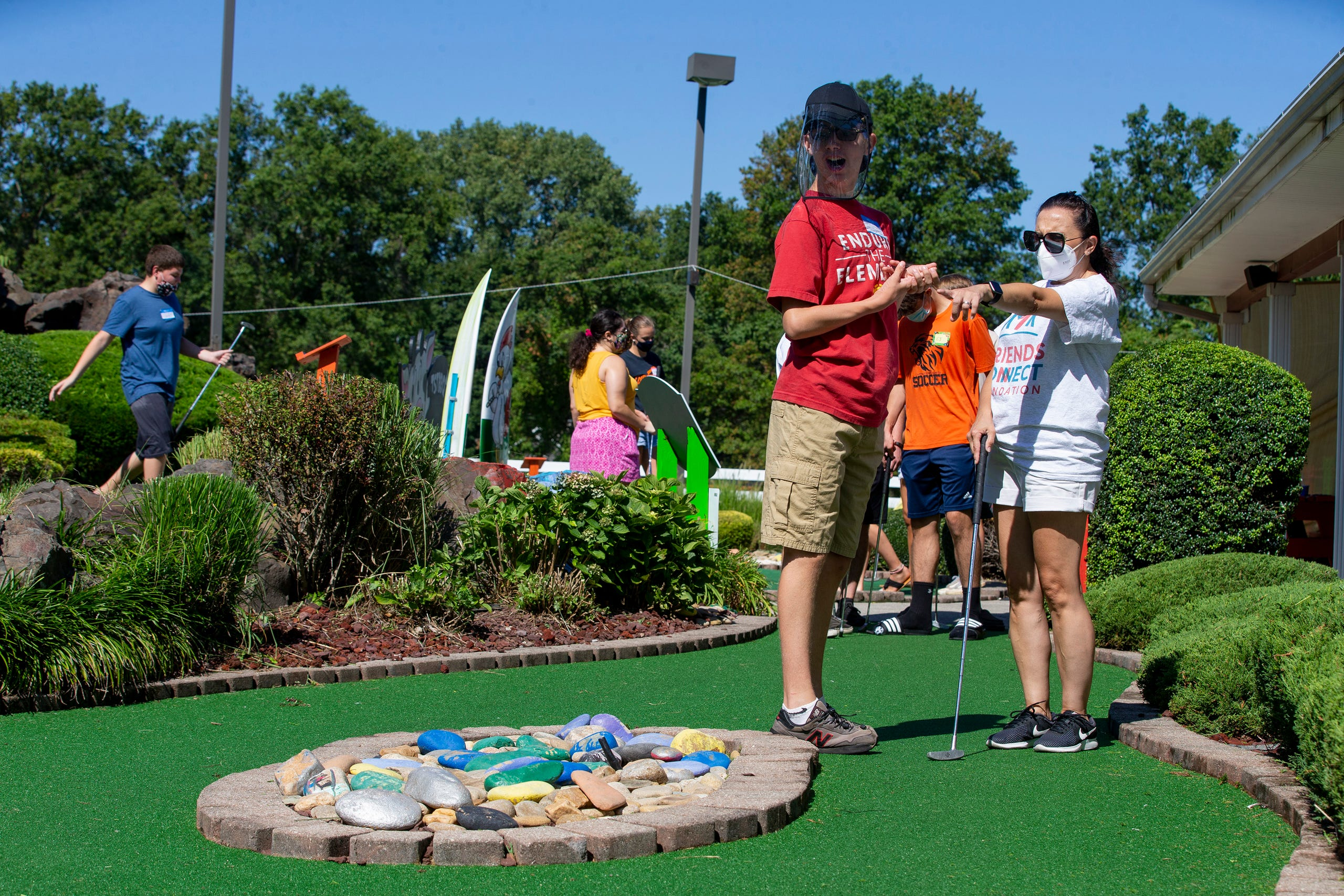 (right) Andrea Ziajski of Middletown, a volunteer with the Friends Connect Foundation, teaches (left) Matty Driscoll, 16, of Fair Haven to golf as members of the Middletown North boys soccer team play mini-golf with a group of special-needs kids as part of Friends Connect Foundation at TST BBQ & Mini Golf in Middletown, NJ Tuesday, August 18, 2020.