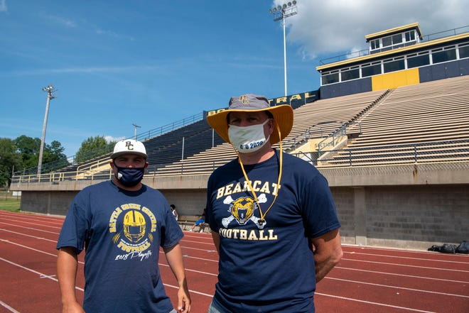 Battle Creek Central assistant coach Casey Bess and head coach Lorin Granger stand for a picture the Monday after MHSAA postponed the season until spring, pictured on Aug. 17, 2020.