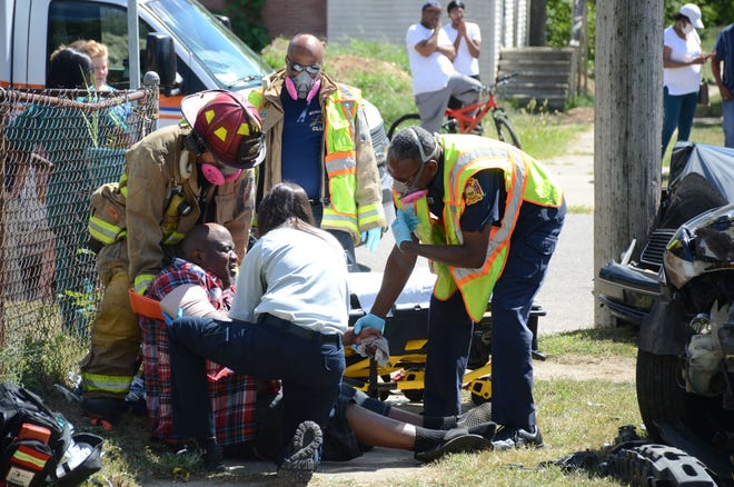 Paramedics from Lifecare Ambulance and Battle Creek firefighters assist a man who was a passenger in one of two cars which collided Tuesday at the intersection of Kendall Street and Roseneath Avenue.  Trace Christenson/The Enquirer