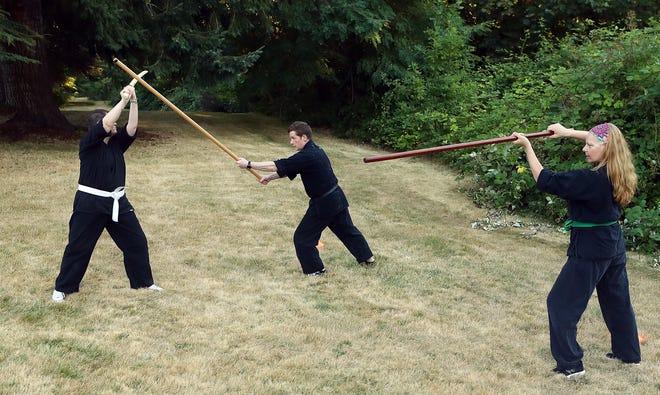 Kitsap Martial Arts instructor Brian Church (center) and students Ginger Vaughan (left) and Barbara Krystal (right) run through a rokushaku bo and sword drill during Church's adult Bujinkan Budo Taijutsu class at Raab Park in Poulsbo on Monday, Aug. 17, 2020.