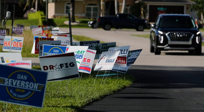 Campaign signs line the entrance driveway to the Cape Coral Library Tuesday, August 18, 2020, as voters make their way to the voting precinct on Election Day.