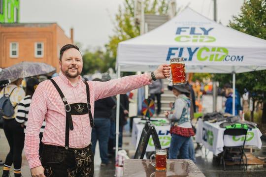 Image from Iowa City Brewfest/Northside Oktoberfest 2019. Iowa City Downtown District Night Mayor Joe Riley runs the Masskrugstemmen/Stein Holding contest in its first year.