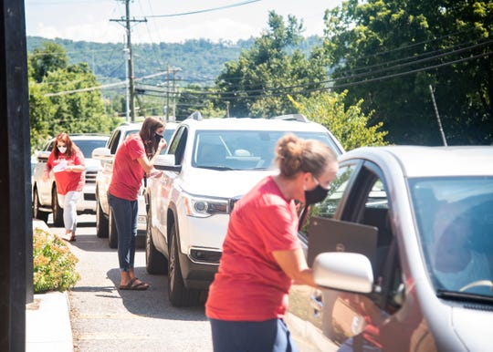 Staff members help out a line of cars waiting for Chromebooks for virtual learning students in front of Halls Elementary School in Knoxville, Tenn., on Tuesday, Aug. 18, 2020.