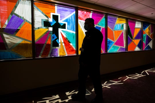 Norton Children's and Women's Hospital chaplain Adam Ruiz walks past a Christian cross created in a stained glass imitation inside the hospital. July 29, 2020