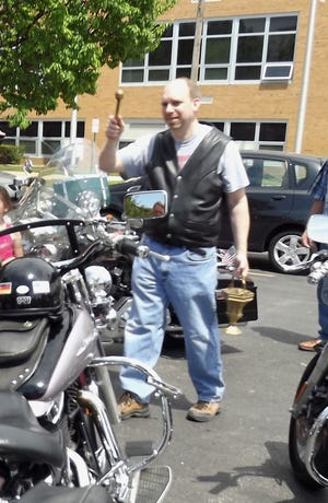 The Rev. Michael Zacharias, pastor of St. Joseph Catholic Church in Fremont, stands among the crowd in the church parking lot blessing the motorcycles and their riders in June 2014. After the blessing, the riders, including Father Mike, took off on their bikes for about an hour ride.