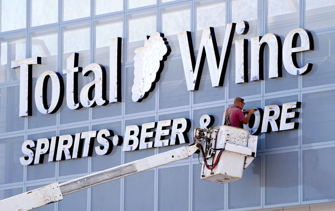 Crews erect the sign for Total Wine & More at Bayshore on Aug. 18. The store opened Thursday, Sept. 3.
