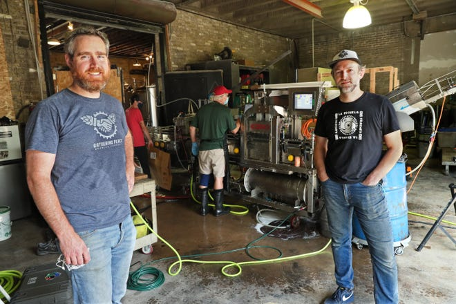 Joe Yeado, left, owner of Gathering Place Brewing, said the Riverwest Syndicate breweries help each other out. Yeado experienced that firsthand when he had his beer canned at nearby Company Brewing. Company is owned by George Bregar, right. Mobile beverage canner WilCraft Can assisted.