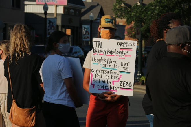 A protester stands with a sign at the Franklin demonstration Aug. 17, 2020, which was organized to stand against a bill that would make camping on state property overnight a felony.