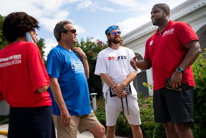 Byron Donalds, right, Republican primary candidate for Florida's 19th congressional district, talks to volunteers during primary election day outside of precinct 251 at the Collier County library headquarters in Naples on Tuesday, August 18, 2020.