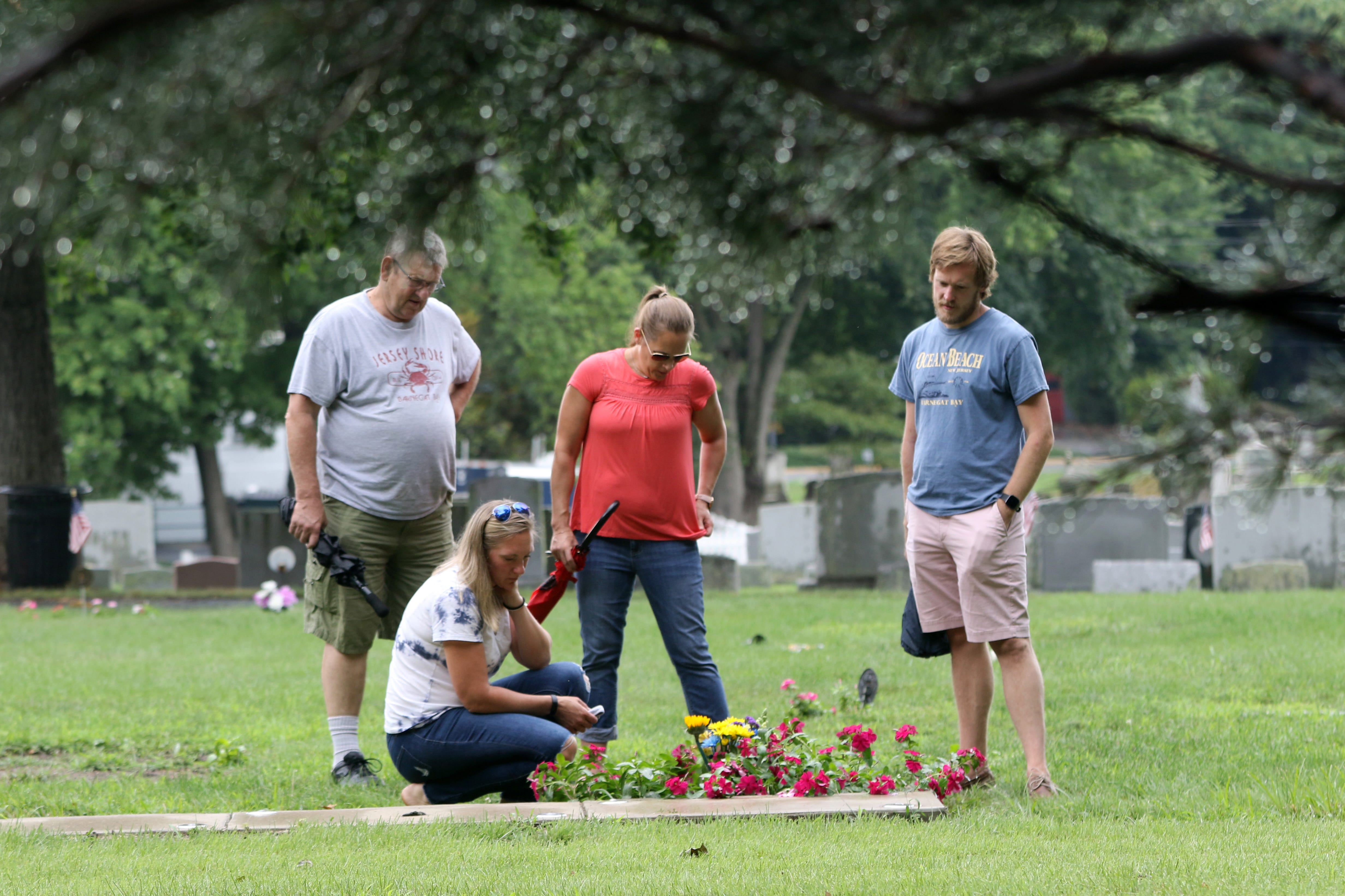 Bill Birchenough, Kristin Carbone (kneeling), Kerri Acuna and Matt Birchenough remember  Barbara Birchenough at her plot, at the Wyckoff Reformed Church Cemetery.  Birchenough worked as a Registered Nurse for Clara Maass Medical Center, where she died of COVID-19, in April, just after her 65th birthday.   Monday, August 17, 2020