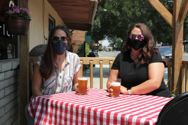 550 Brewing co-owners Micah Fiske, left, and Ericah Boyd, right, seen here on Tuesday, Aug. 18, 2020, sit in the restaurant's sidewalk patio area in front of Main Avenue in downtown Aztec.