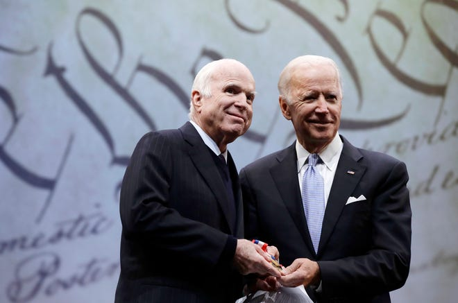 Sen. John McCain, R-Ariz., left, receives the Liberty Medal from the chairman of the National Constitution Center's board of trustees, former Vice President Joe Biden, in 2017. In 2015, when President Donald Trump was running for his first term, he said McCain was not a war hero because he was captured while serving in Vietnam.