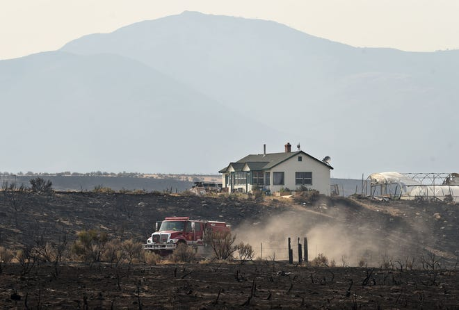 A fire truck moves past a house that the Loyalton Fire got dangerously close to just west of the Long Valley Border Station on U.S. 395, 21 miles north of Reno on Monday, August 17, 2020