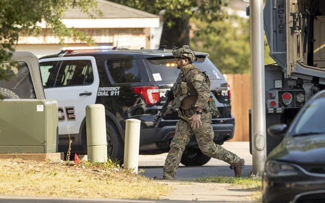An officer walks near the scene of a standoff in Cedar Park, Texas, on Sunday, Aug. 16, 2020. Police closed off access to the street and eventually cut power to an area near the home of the shooter. Around noon on Sunday a shootout resulted in three officers being shot with the shooter barricading in their home with members of their family.