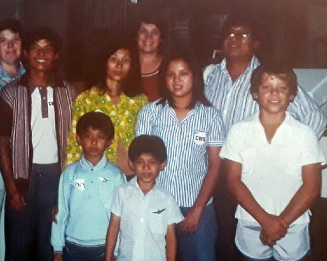 Phoung and Chuon Ngo, from left, and William Ramsey, right, line the front row as the Barbara Ramsey family of Texas met the arriving Ngo refugee family from Vietnam at the Dallas airport in the early 1980s.
