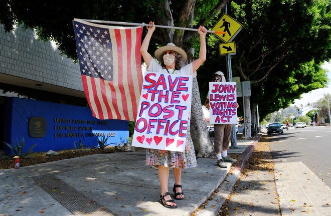Erica Koesler, left, and David Haerle, both of Los Angeles, demonstrate outside a USPS post office, Aug. 15, 2020, in the Los Feliz section of Los Angeles. The USPS has warned states coast to coast that it cannot guarantee all ballots cast by mail for the November election will arrive in time to be counted, even if mailed by state deadlines, raising the possibility that millions of voters could be disenfranchised.
