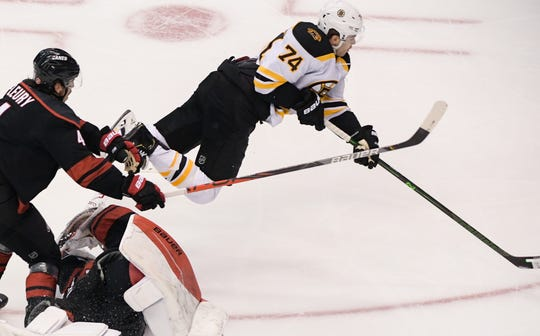 Boston Bruins left wing Jake DeBrusk goes airborne after colliding with Carolina Hurricanes goaltender James Reimer but manages to score.