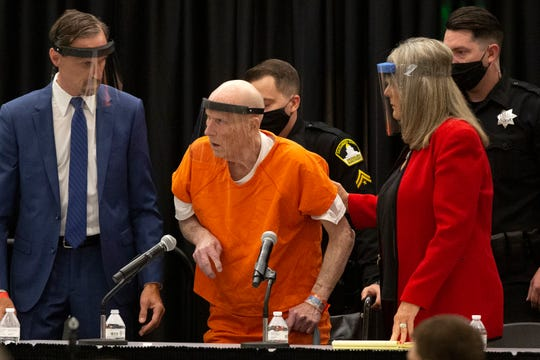 In this June 29, 2020, file photo, Joseph James DeAngelo, center, charged with being the Golden State Killer, is helped up by his attorney, Diane Howard, as Sacramento Superior Court Judge Michael Bowman enters the courtroom in Sacramento, Calif.