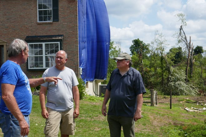 Neighbors on Country Brook Drive in Doylestown Township discuss the tornado that  damaged their homes and property on Aug. 4.  From left are: Adam Skelding, Marc Hansen, who's home in background will be demolished, and Michael Haggerty, whose home also was heavily damaged.