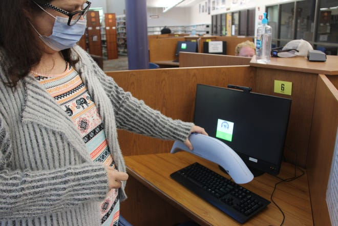 An employee at the Ardmore Public Library uses an ultraviolet light disinfecting device to sterilize a computer. The device was purchased with funds from the CARES Act grant.