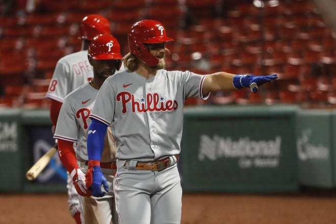 Phillies right fielder Bryce Harper waves to teammates sitting in the stands after hitting a three-run home run against the Red Sox during the sixth inning Tuesday.